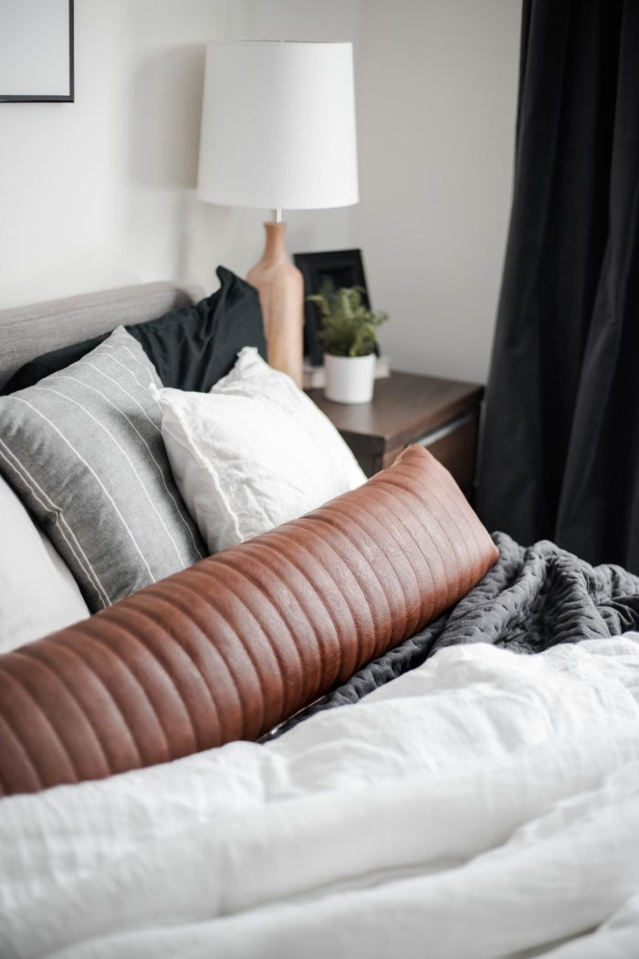 Extra long channel leather lumbar pillow on black and white bedding.