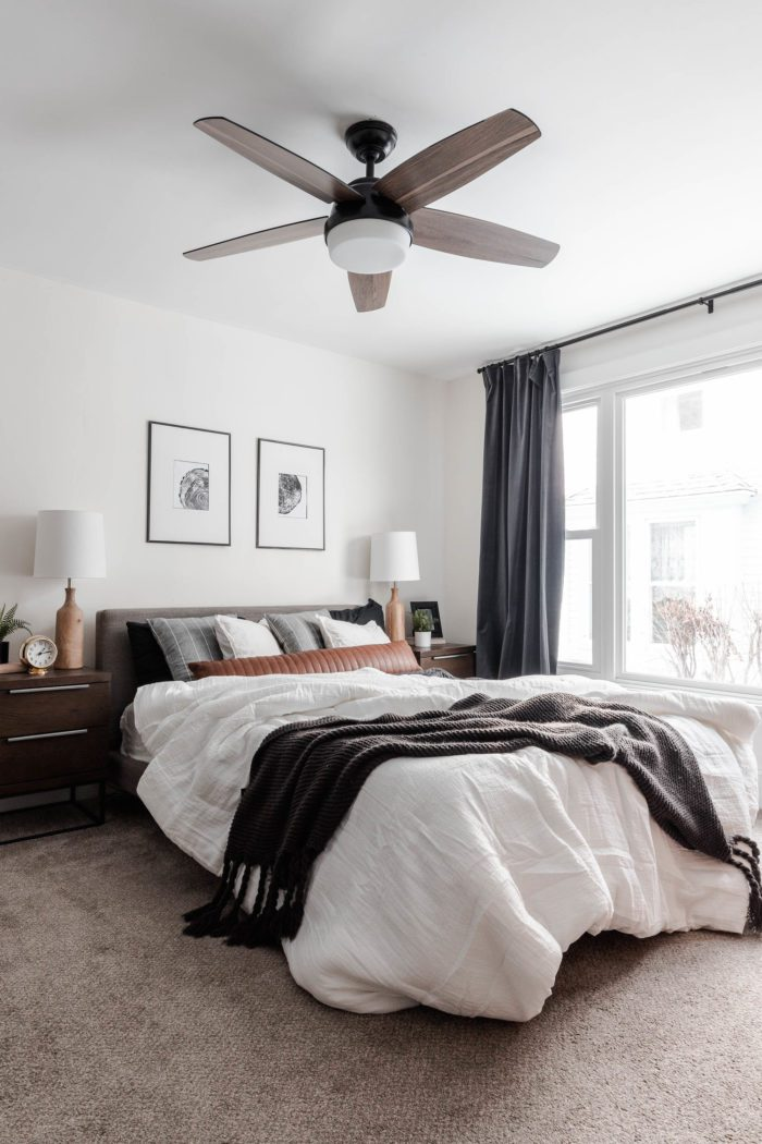 The Messy Look: featuring a lived in look. Queen size bed with a modern gray headboard, white bedding, dark gray accents and a leather lumbar pillow with layered white pillows and gray throw pillows.