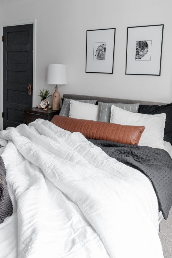 How to Make Your Bed like a Designer Queen size bed with a modern gray headboard, white bedding, dark gray accents and a leather lumbar pillow. All with a messy, cozy, lived in look!