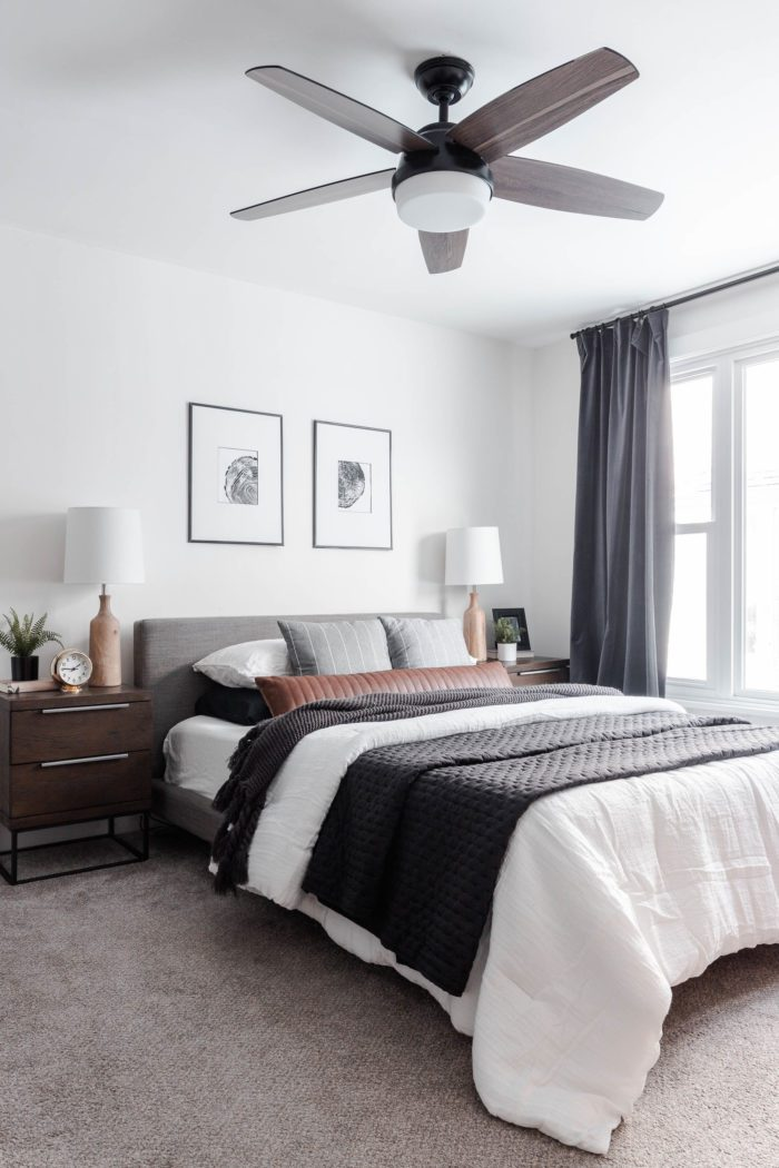 How to Make Your Bed like a Designer: Queen size bed with a modern gray headboard, white bedding, dark gray accents and a leather lumbar pillow.