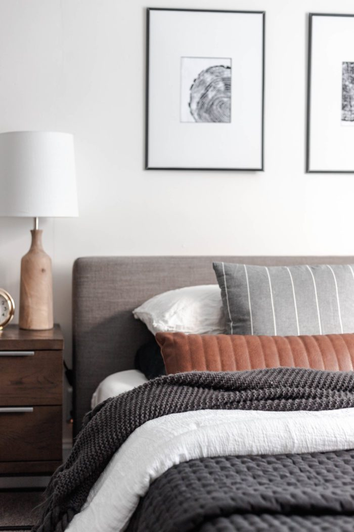 How to Make Your Bed like a Designer - The layered look: Queen size bed with a modern gray headboard, white bedding, dark gray accents and a leather lumbar pillow.