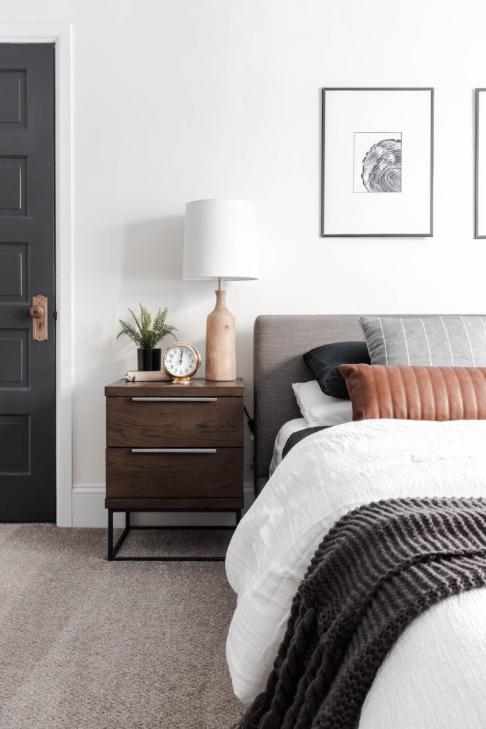 How to Make Your Bed like a Designer! Queen size bed with a modern gray headboard, white bedding, dark gray accents and a leather lumbar pillow.