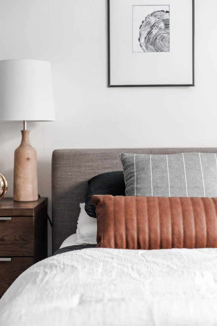 The Streamlined looks featuring clean lines. Queen size bed with a modern gray headboard, white bedding, dark gray accents and a leather lumbar pillow.
