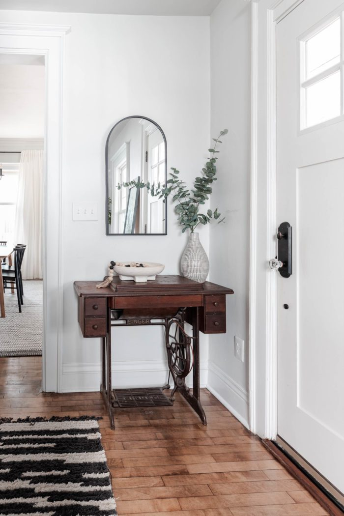 Old singer sewing machine mixed with modern decor. An arched mirror hangs above with a pedestal bowl and tall vase with faux branches to frame it out!