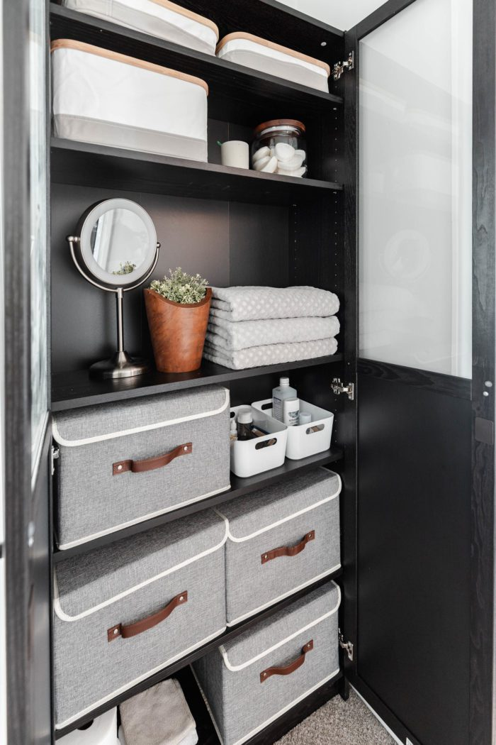 Storage bins used inside of an Ikea Billy Bookcase to create functional organization when your bathroom lacks storage.