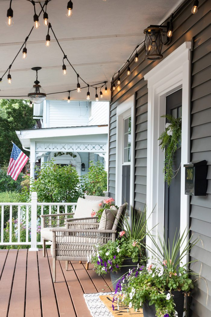 Summer Outdoor Furniture on front porch with flowers on either side of the front door.