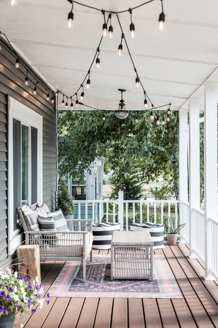 Summer Outdoor Furniture on front porch with rug and flowers