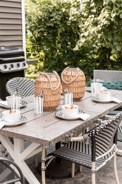 Outdoor Summer Table Decor with 2 lanterns and fresh fruit served in a white bowl.