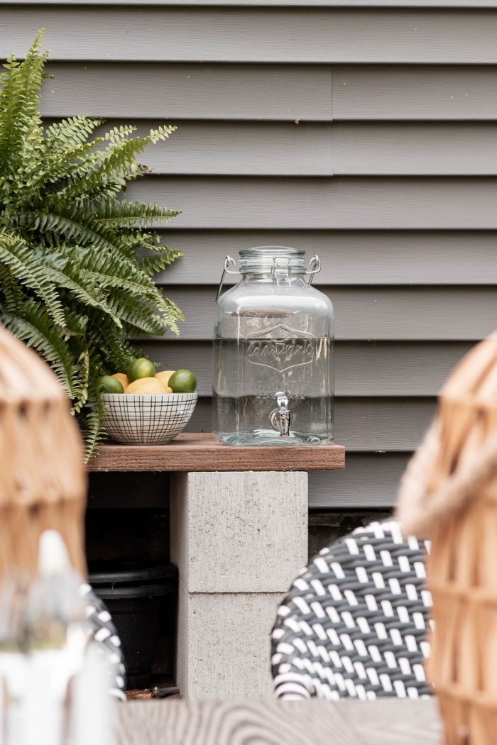 Glass water dispenser used outdoors on a potting bench next to a fern plant.