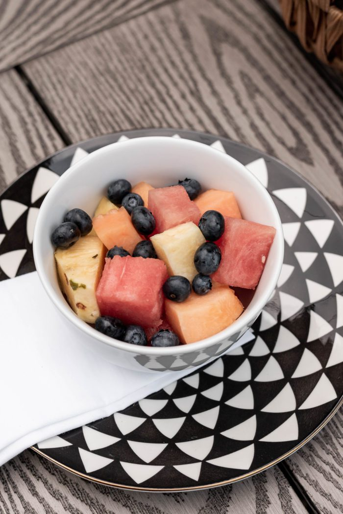 Fresh tropical fruit in white bowl served as part of a fun summer table setting.
