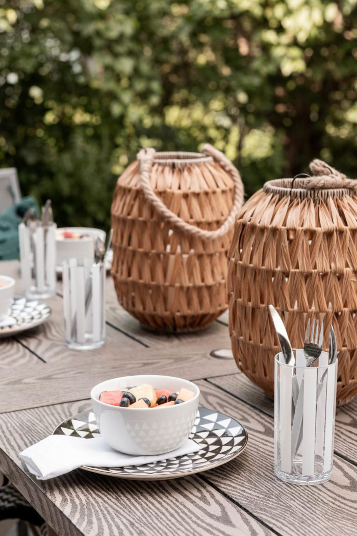Outdoor wicker lanterns used as a centerpiece for a Summer Table Setting.