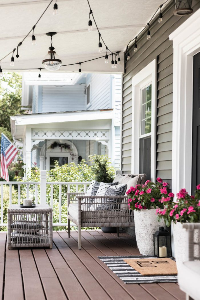 Front porch with white planters, loveseat and coffee table - Easy Summer Porch Decor Ideas