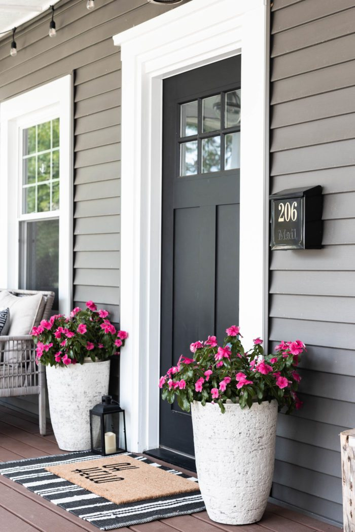Tall planters on either side of front door with layered rugs creating the perfect summer spot!