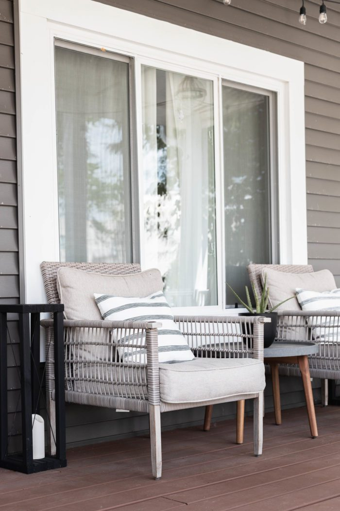 Outdoor furniture on front porch decorated for summer.