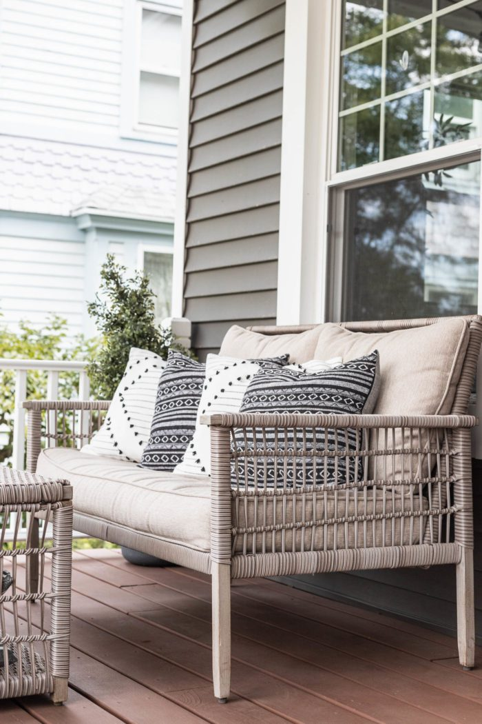 Black and White pillows layered on an outdoor loveseat.