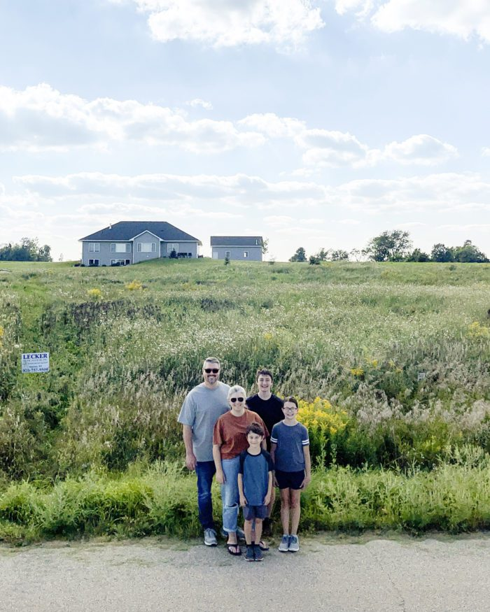 We are building a home! Our family standing in front of our new piece of property!